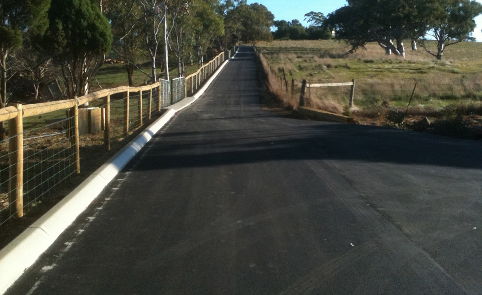 Long asphalt drive in country with curbing